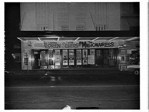 Night exterior of the Century Theatre advertising the film The millionairess