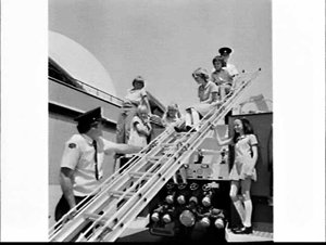 Children from Macquarie Fields Public School assist the Fire Brigade at the official opening of Fire Prevention Week 1979 in the forecourt, Sydney Opera House