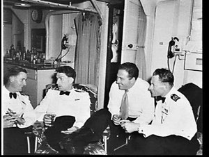Officers in dress uniform having a drink on HMAS Anzac at sea en route for Malaya and Singapore