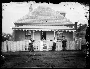 Group with unidentified rendered house with shingle roof, veranda and picket fence