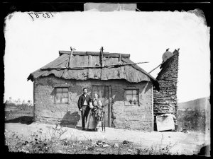 Henry Hunt (?), wife and child and house, Hill End