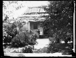Woman and child outside a bark roof house, Hill End