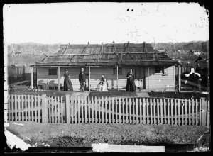 Man and women on the veranda of their weatherboard house with bark roof and picket fence, Gulgong
