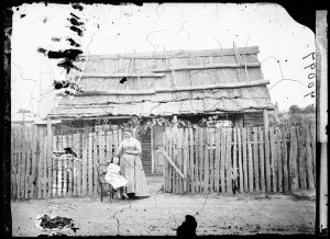 Woman and child in front of bark roof, weatherboard house with paling fence, Hill End