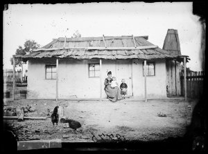 Woman and children with whitewashed house and bark roof, Hill End