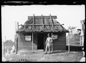 Portrait of man in suit and bowler hat in front of weatherboard cottage with bark roof belonging to Alston Balmanno Ferrie, auctioneer, Gulgong