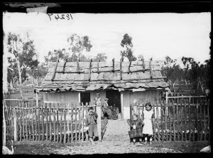 Family outside a slab house with bark roof, Gulgong