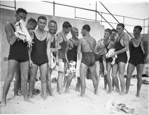 """[Young male surfers (""""The Pier Club Mob"""") tease Alf """"Bait"""" Gould about his backless swimsuit (a gift from his girlfriend), Bondi Beach]"""