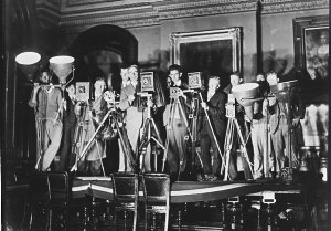 Press photographers and one newsreel man photograph the dismissal of the Lang Government; left to right: Cinesound electrician, unknown youth, Sam Hood, Joe Stafford (Cinesound), Bert Fishwick (Sydney Mail), Harry Martin (Sydney Morning Herald), Bill Jackson (The Sun), Ted Hood (Melbourne Argus) and two electricians