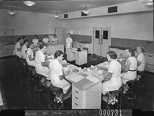 Twelve uniformed women students at a cookery class, Kogarah