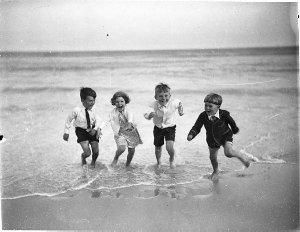 Four young children paddling, fully clothed