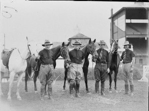 Four riders beside their mounts