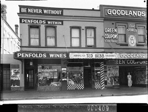 Penfold's Wines display in wine shop window with slogan 'Be Never Without, Penfold's Within'; Ted Webb, hairdresser, next door; then Goodlands (grocers)
