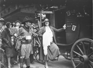 """Gladys Moncrieff assisted into stage coach by actor-cowboy (""""Buy a poppy from Gladys Moncrieff, 1/"""") on Remembrance Day, State Theatre"""