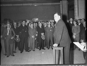 Mr Morrow speaking to a crowd of men in the demonstration hall, Timber Homes Display