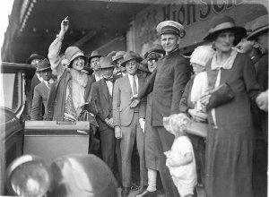 First Miss Australia, Beryl Mills, getting into her new Chrysler convertible, while the commissionaire holds back the crowds, Haymarket Theatre