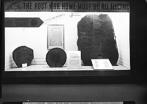 """Timber Homes Exhibition: notice reads; """"The post war home must be all electric"""" in a city shop window (?)"""
