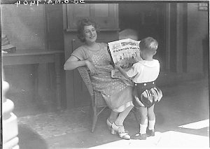 Musical comedy star Dorothy Brunton showing Sid Nicholl's Fashion-plate Fanny in the children's section of The Sun newspaper to a small boy