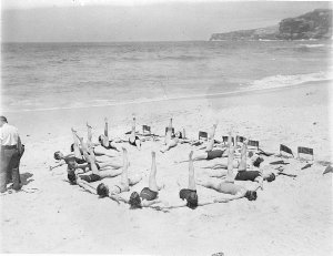 Capitol Theatre chorus girls lie on the sand making a clock face pattern with one leg in the air a la Busby Berkeley