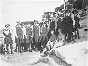 Two teachers in swimming costumes, with Bethlehem College, Ashfield schoolgirls in uniform