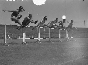 Six competitors clear the first hurdle in the 120 yards