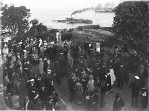 VIPs crowd on the lawn.  General Blamey on right, hand near face.