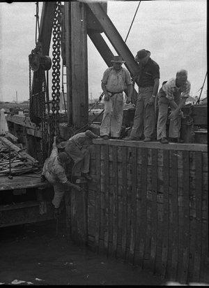 "Main Roads Dept. workmen repair damage caused when the vehicular ferry ""Lurgurena"" hit the landing ramp on the Stockton side"