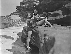 Two Capitol Theatre chorus girls in swimsuits, one combing the other's hair after a swim