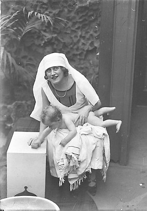 Musical comedy star Dorothy Brunton holding a nude small child grabbing the soap, St. Margaret's Hospital