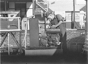 Workman fitting up pumps etc for Buzacott's Machinery Exhibition