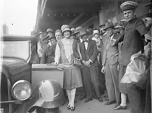 Haymarket Theatre commissionaire holds back the crowd as the first Miss Australia, Beryl Mills, gets into her new Chrysler convertible