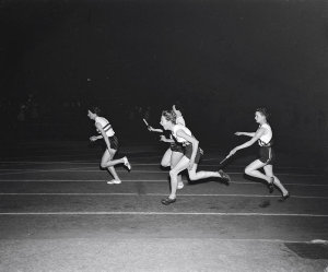 Betty Cuthbert about to take the baton from Fleur Mellor in the 4 x 110 yds. relay to set a new World Record of 45.6 sec. at the British Empire & Commonwealth versus USA 1956 athletic meet
