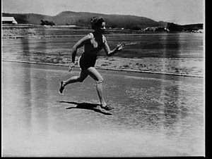 """Marjorie Jackson (the Lithgow Flash) running at a racecourse (with the """"flash"""" on her top)"""