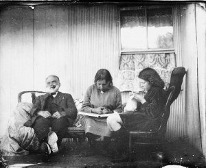 Relaxing on the verandah. Man smoking, girls reading and sewing - Scone area, NSW