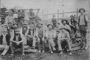 Gold miners seated with pit props. Man with broad axe on right - Coolgardie, WA
