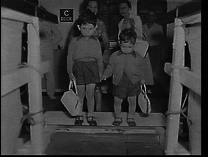 Migrant English boys carrying their mothers' handbags leaving the SS Strathaird