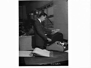 Executive reading a teletype message as it comes from the machine, K.V. Chapman, wool merchants, Pyrmont