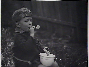 Boy blowing bubbles from pipe
