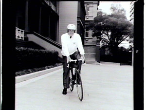 """Minister (Mr M.A. Cleary) with """"stack-hat"""" & bicycle at Parliament House"""