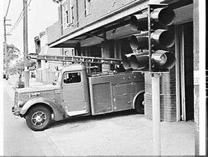 Firemen operate traffic lights from the fire station to speed exit of the fire engine
