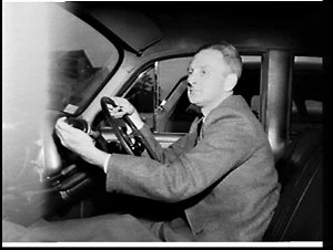 Handicapped man driving car with modified gearstick, Australian Paper Manufacturers, Matraville