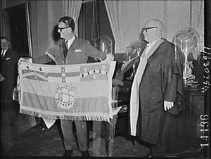 Alistair Urquhart, Chairman, Stock Exchange presents medallion to the Town Clerk of Sydney who presents a City of Sydney flag in return, Town Hall