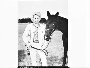 Country & western singer/guitarist Reg Lindsay photographed with horse for TV Times, Centennial Park