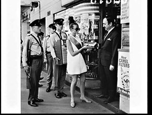 Woman in mini-skirt and MSS security guards deliver cartons of new Belvedere cigarettes to retailers, Sydney