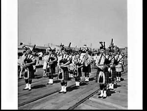 Actress Clare Dunne and her husband and winners of a competition leave on the liner Himalaya (played out by the Epping Pipe Band), no. 13 Wharf Pyrmont
