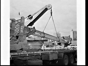 Calweld hole-digger unloaded from ship (?) and loaded onto a semi-trailer, Woolloomooloo Wharf
