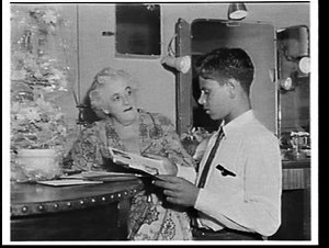 Margaret Rutherford giving her autograph to Tom Cain, an Aboriginal boy, in her dressing room at the Elizabethan Theatre