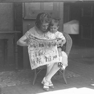 Musical comedy star Dorothy Brunton reading Sid Nicholl's Fashion-plate Fanny in the children's section of The Sun newspaper with a small boy at St. Margaret's Hospital