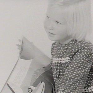 Three-year old reading books (for cover of publication)