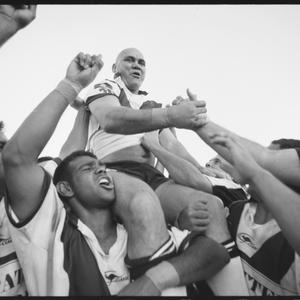 Item 05: Grand final winners of the 34 Koori Knockout, the Cec Patten-Ron Merritt Memorial Redfern All Blacks lift captain Graeme Merritt in the air after the game, Redfern Oval, Sydney, Monday, 4 October 2004 / photograph by Jamie James